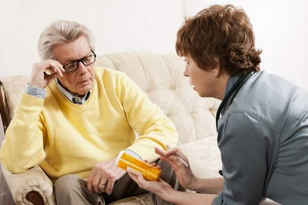 Medical provider explaining perscription instructions to elderly man