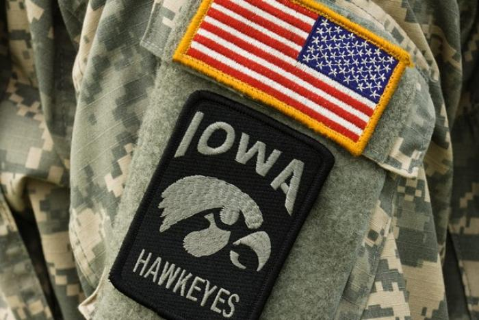 United States of America flag patch above Iowa Hawkeye logo patch on shoulder of a military uniform.